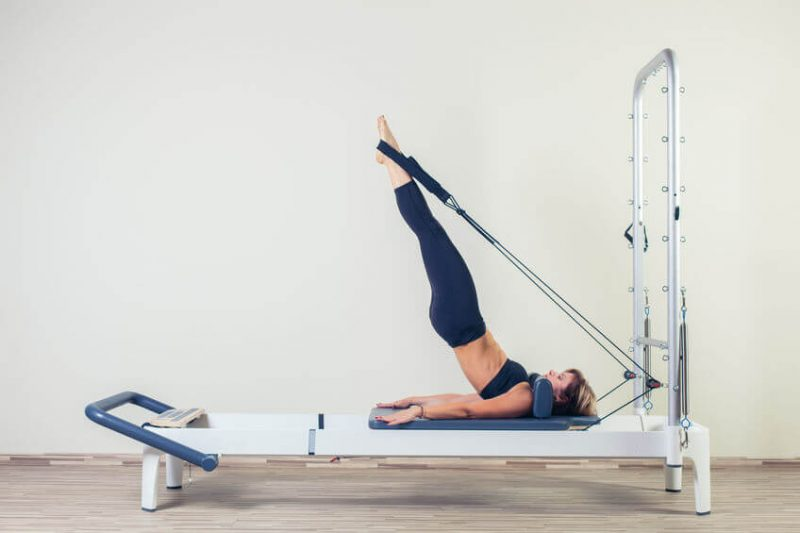 Pilates reformer workout exercises woman at gym