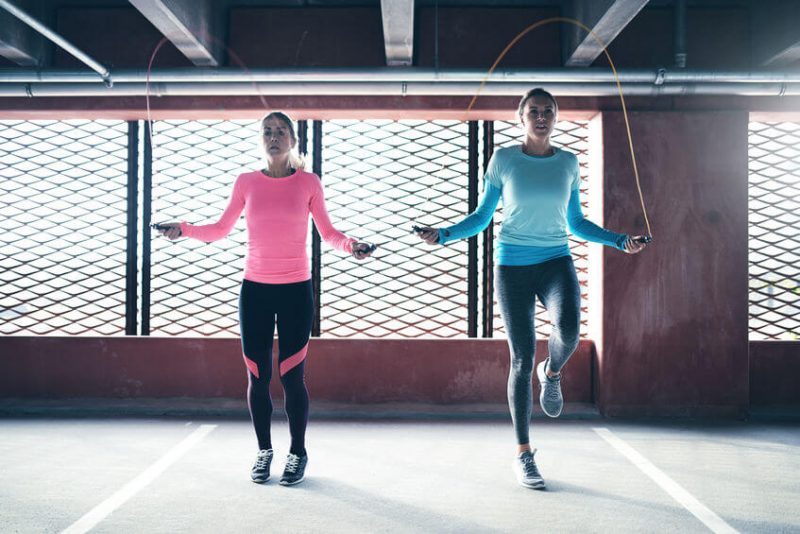 two athletic girls doing jump rope exercise